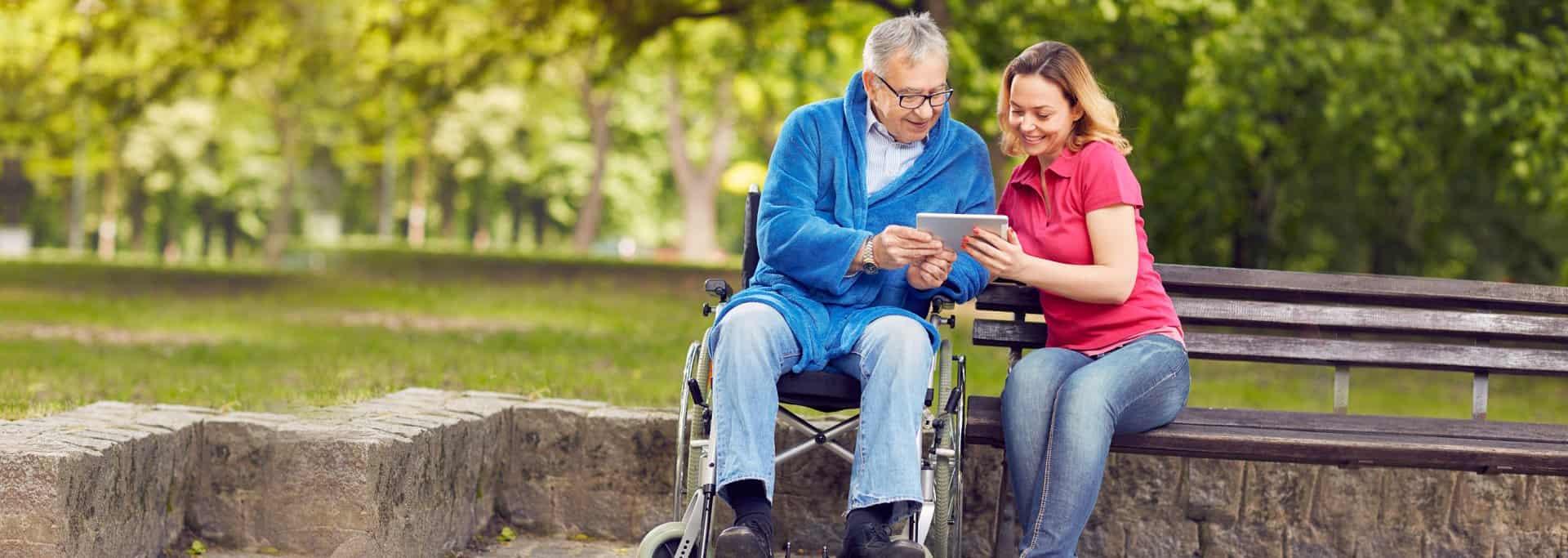 caregiver and elder man looking to gadget