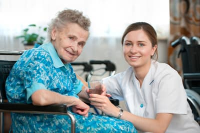 elder woman with her caregiver at home smiling