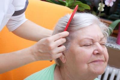 caregiver combing elder woman's hair