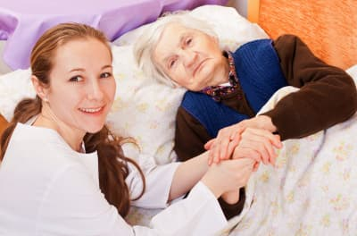 caregiver holding elder woman's hands