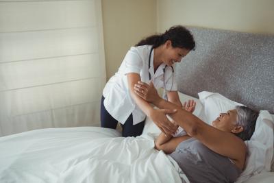 caregiver assisting elder woman on bed at home